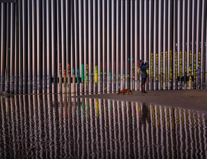A woman takes a snapshot by the border fence between San Diego, Calif., and Tijuana, as seen from Mexico, Thursday, Jan. 3, 2019.
