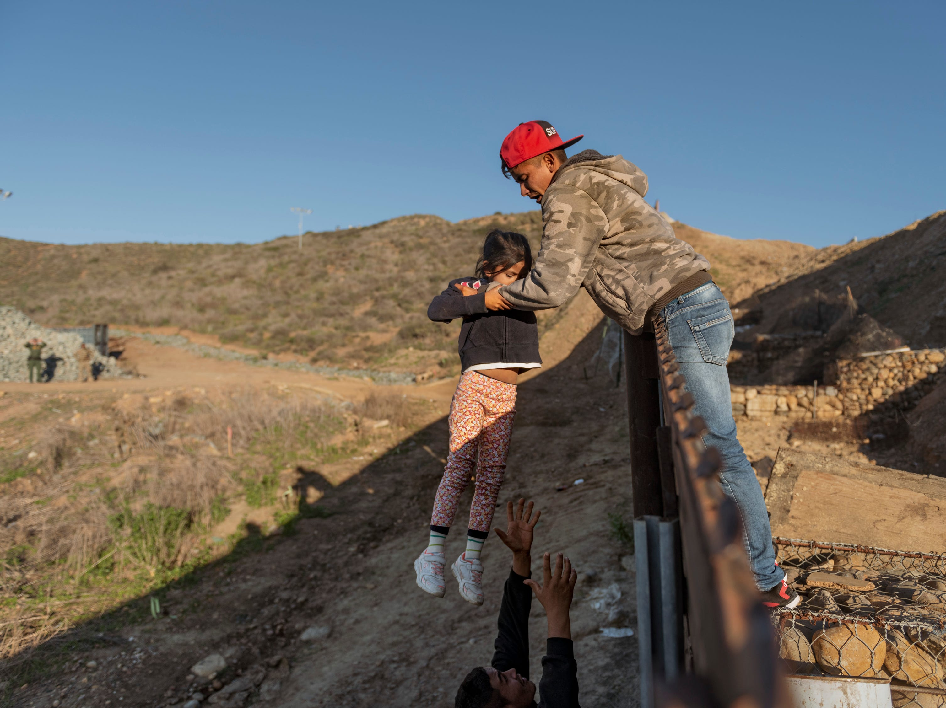 A migrant from Honduras pass a child to her father after he jumped the border fence to get into the U.S. side to San Diego, Calif., from Tijuana, Mexico, Thursday, Jan. 3, 2019.