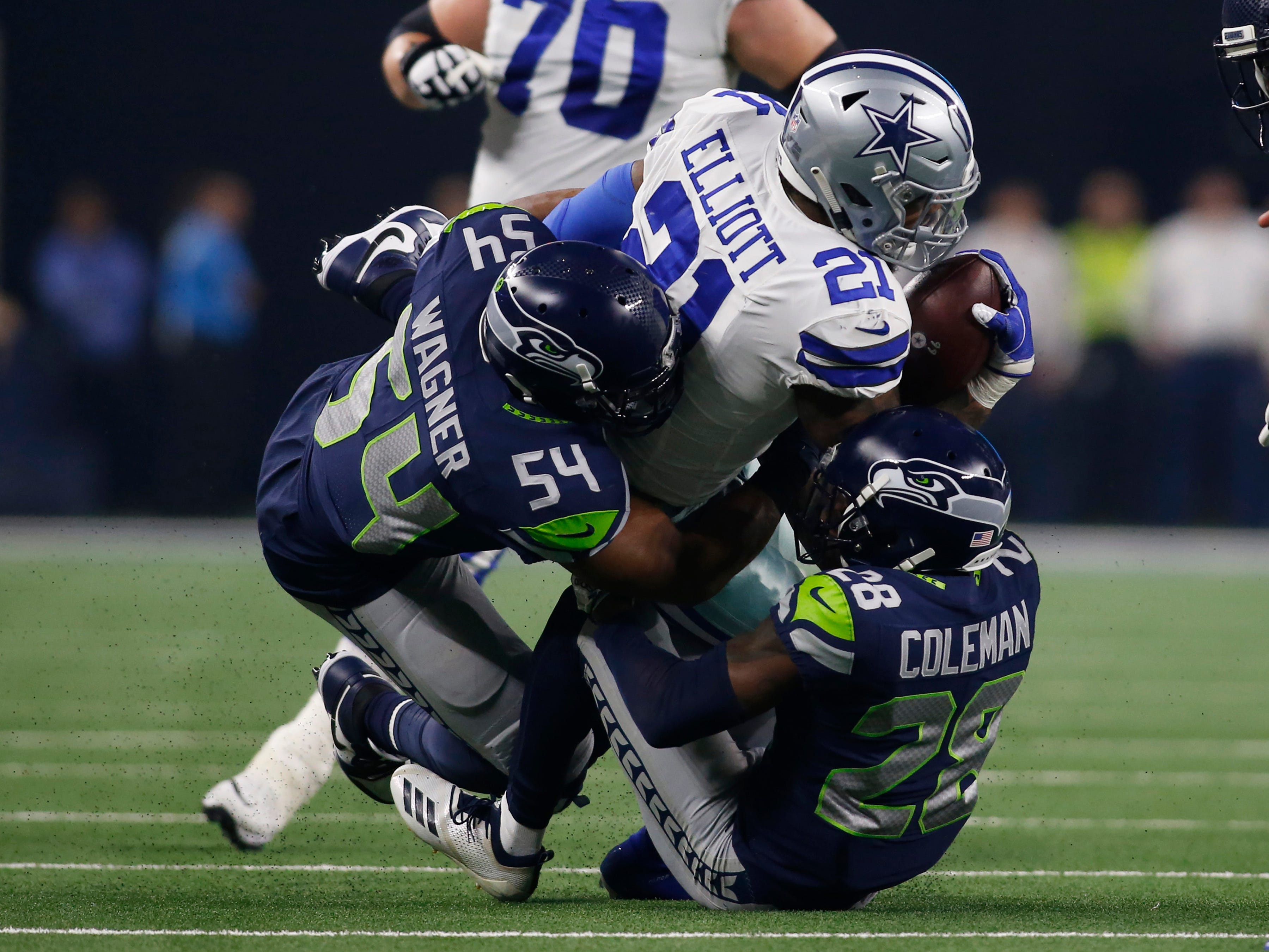 Dallas Cowboys running back Ezekiel Elliott (21) is tackled by Seattle Seahawks cornerback Justin Coleman (28) and linebacker Bobby Wagner (54) in the first quarter at AT&T Stadium.