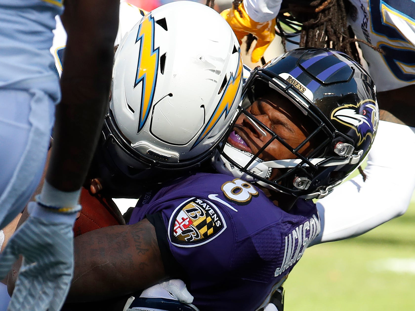 Baltimore Ravens quarterback Lamar Jackson (8) is tackled by Los Angeles Chargers defensive end Joey Bosa (99) in the first quarter in a AFC Wild Card playoff football game at M&T Bank Stadium.