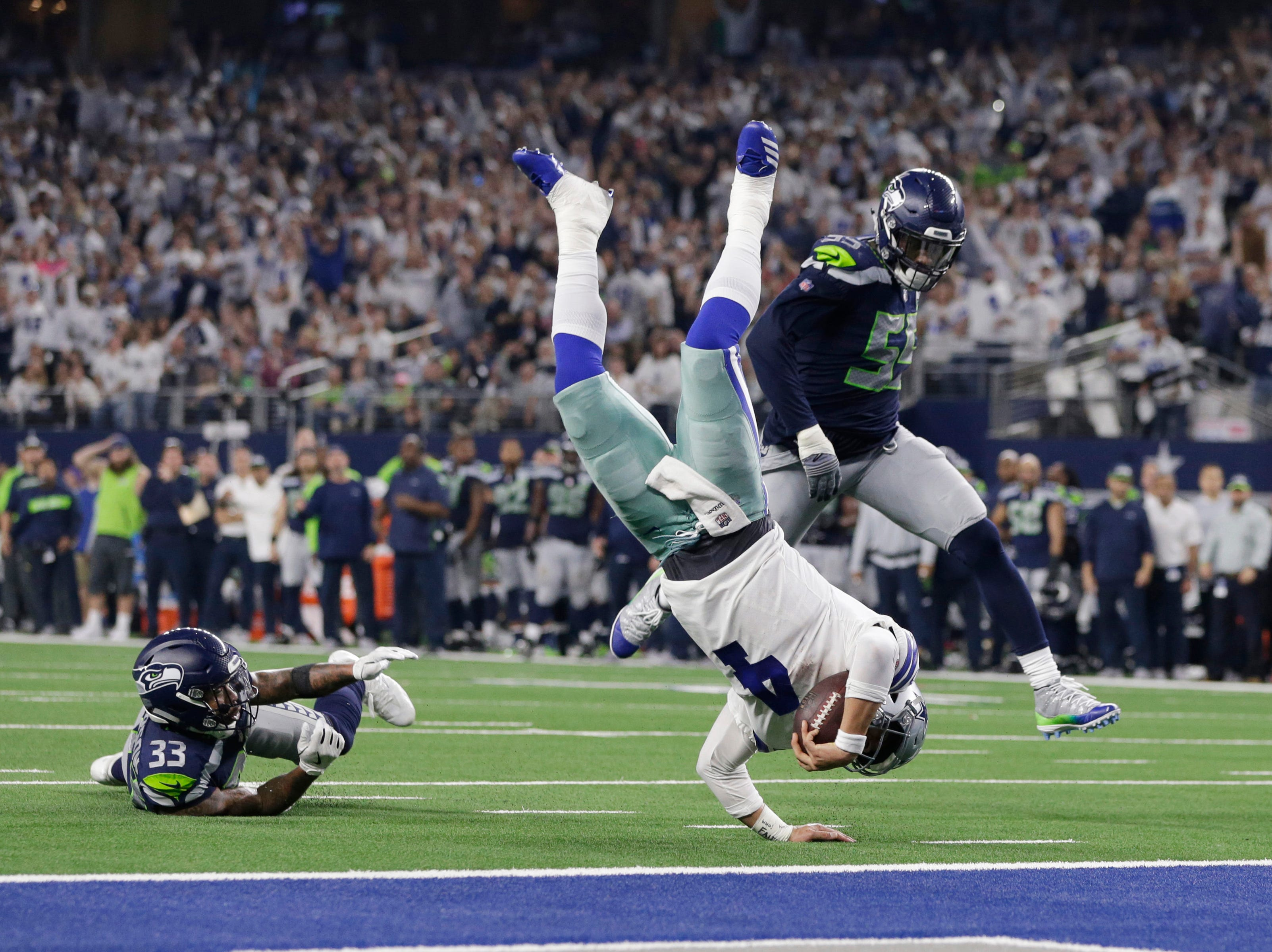 Dallas Cowboys quarterback Dak Prescott (4) is tackled at the 1-yard line by Seattle Seahawks free safety Tedric Thompson (33) in the fourth quarter at AT&T Stadium.