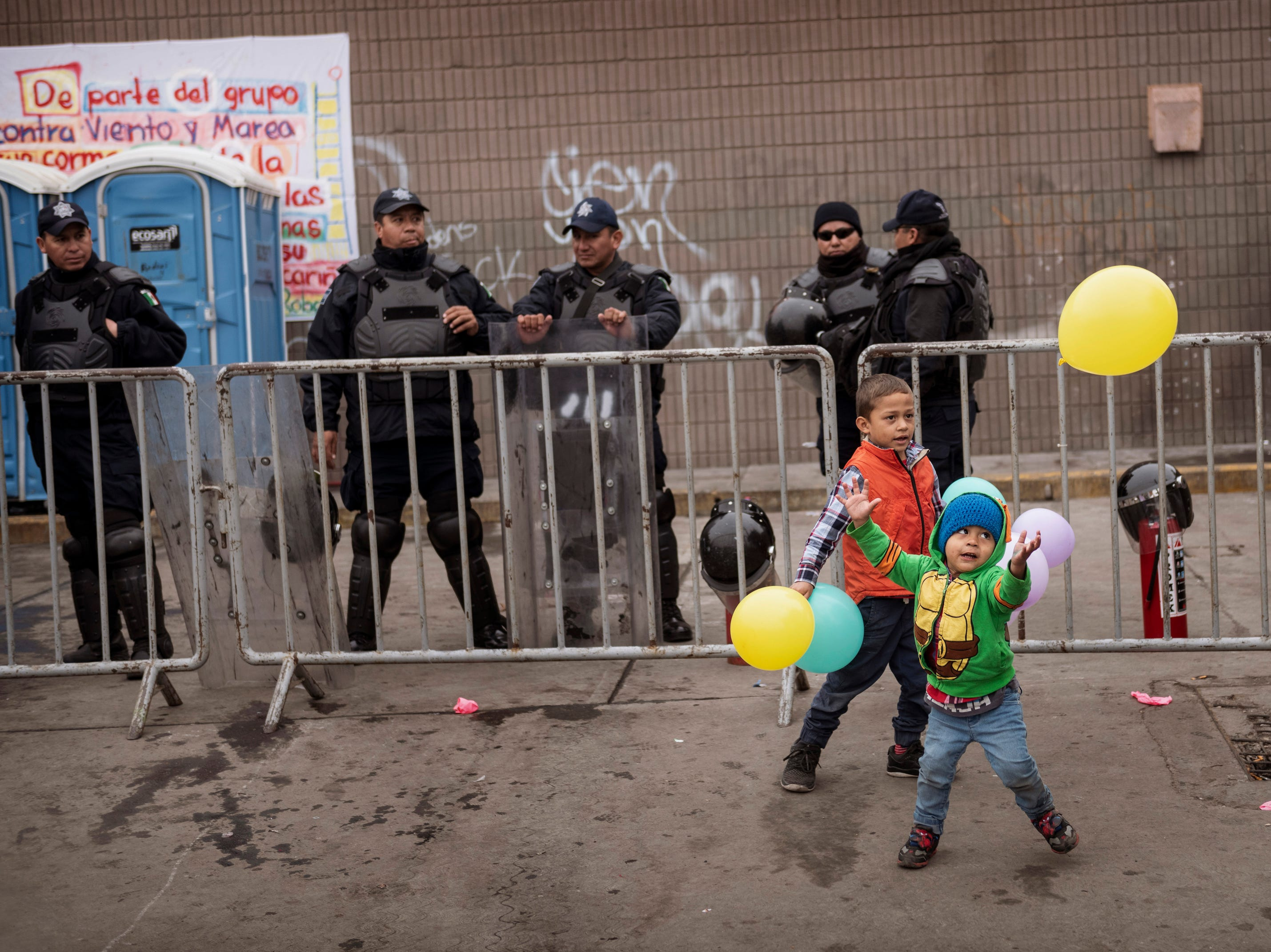 Children play with balloons in front of Federal Police outside an empty warehouse used as a shelter set up for migrants in downtown Tijuana, Mexico, Saturday, Jan. 5, 2019. Authorities ordered the shelter to be closed due to sanitary conditions. Discouraged by the long wait to apply for asylum through official ports of entry, many migrants from recent caravans are choosing to cross the U.S. border wall and hand themselves in to border patrol agents.