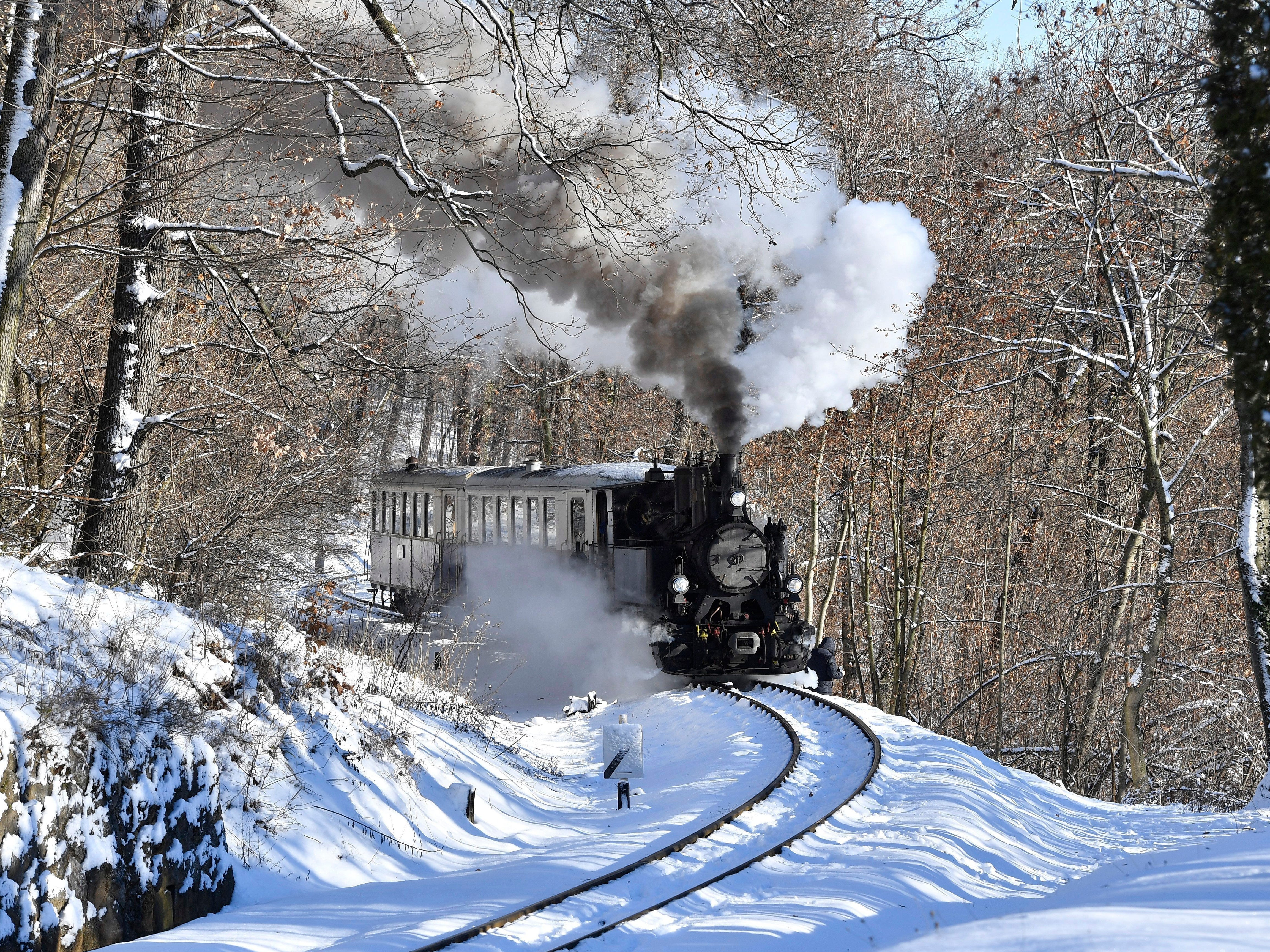A nostalgic train pulled by a 490 steam engine drives through a winterly landscape on its way to the Szepjuhaszne station of the Children's Railway, in Budapest, Hungary on Jan. 6, 2019. Except the engine's driver all posts on the train are traditionally operated by children at the age of between 10 and 14 years. The Children's Railway is an 11 kilometers long narrow gauge line between Szechenyi-hegy and Huvosvolgy in the Hungarian capital.