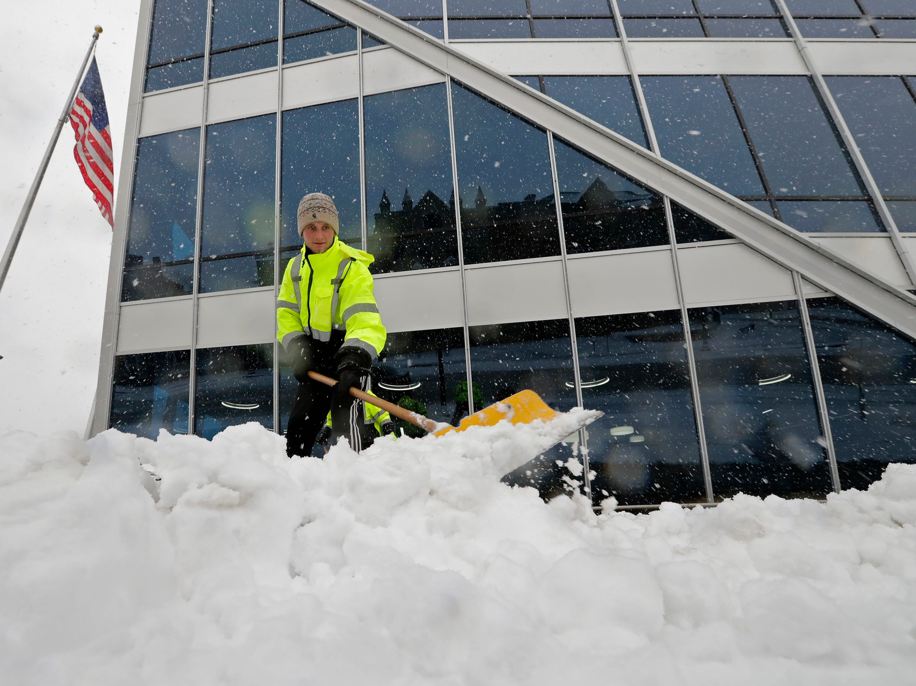 Clayton Leitner, an employee with Stumpf Creative Landscapes, shovels snow in front of the Menasha One building during a snow storm Monday, December 31, 2018, in downtown Menasha, Wis. Dan Powers/USA TODAY NETWORK-Wisconsin