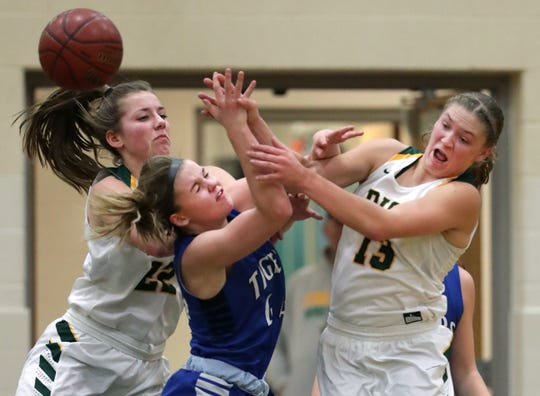 Freedom's Taylor Haase, left, and Gabby Johnson battle for the ball with Wrightstown's Ella Diny during a North Eastern Conference basketball game Jan. 3 in Freedom.