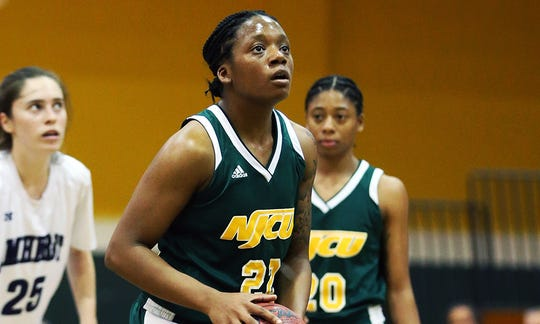 Miesha Bacon shoots a free throw with sister Marajiah Bacon in the background.