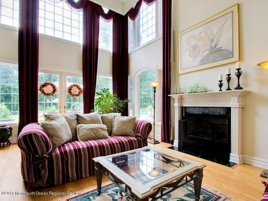 The great room features custom windows, vaulted ceiling, and decorative crown molding.