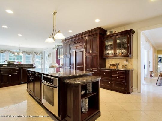 The kitchen features custom cherry cabinets, oversized island, granite counters, and professional appliances.