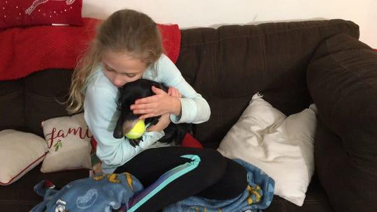 Loralie Cote, 9, cradles Jersey in her Hazler home