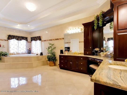 The master suite features his and hers custom sinks, sumptuous bath with steam shower and Jacuzzi.