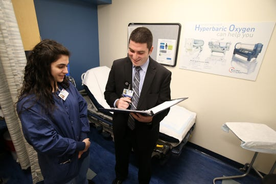 Christina Gulotta, 17, a senior at Monmouth County Vocational's Academy of Allied Health and Science, looks over a chart with Dr. Eugene Zurkovsky, a general surgeon, in the wound care center at Jersey Shore University Medical Center in Neptune, NJ Monday, January 7, 2019.