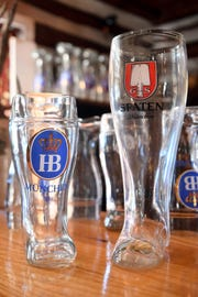 Boot glasses for beer sit on the bar at the Bavarian Restaurant & Biergarten.
