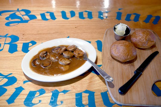 The Pot Luck Bratwurst Sampler at the Bavarian Restaurant & Biergarten is sauteed with sweet onion gravy and served with German bread & herb butter.