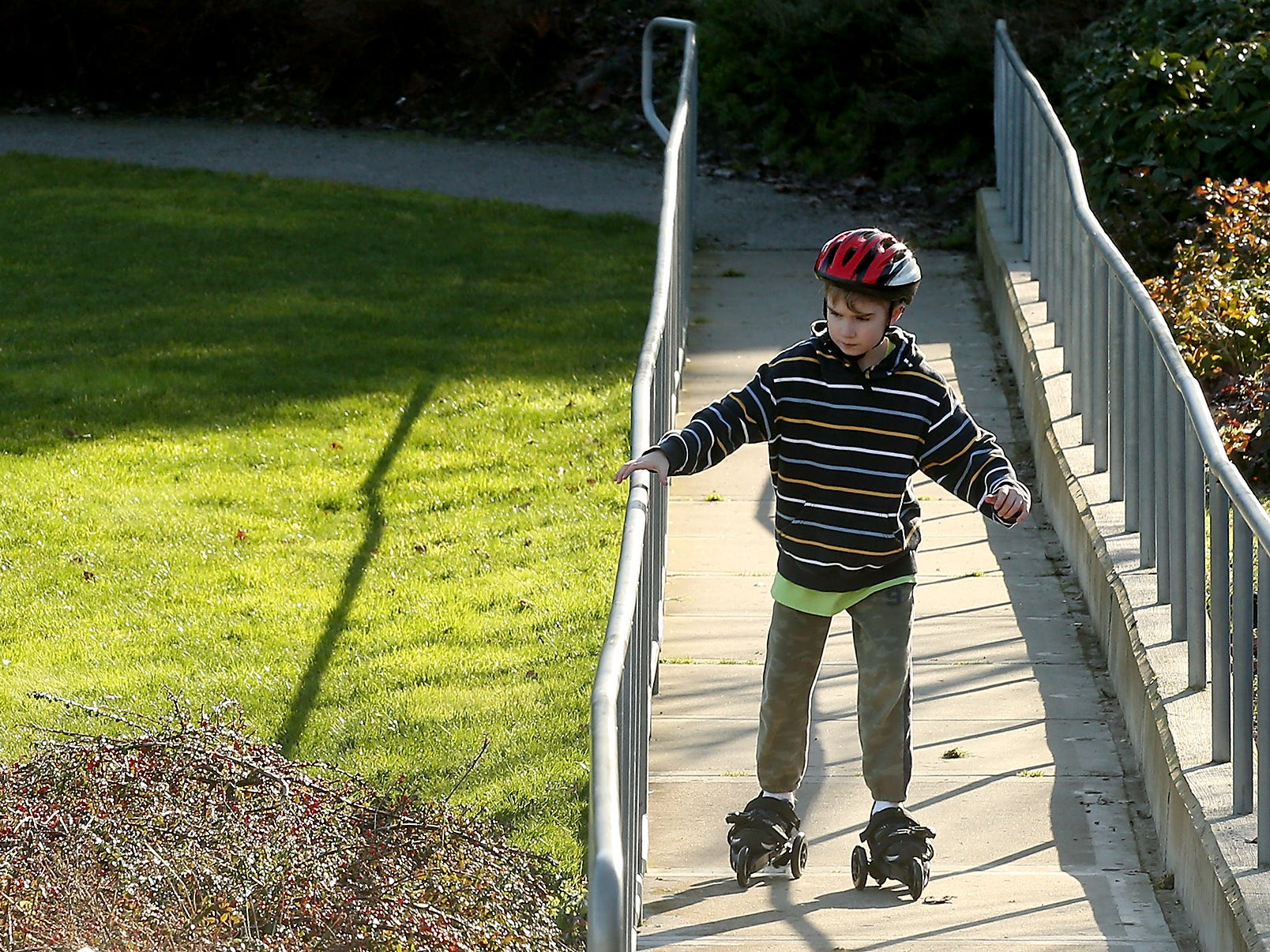 Gavin Tiemeyer, 8, grabs the railing as tries out the new skates that he received for Christmas at Kiwanis Park in Bremerton, on Monday, January 7, 2019.