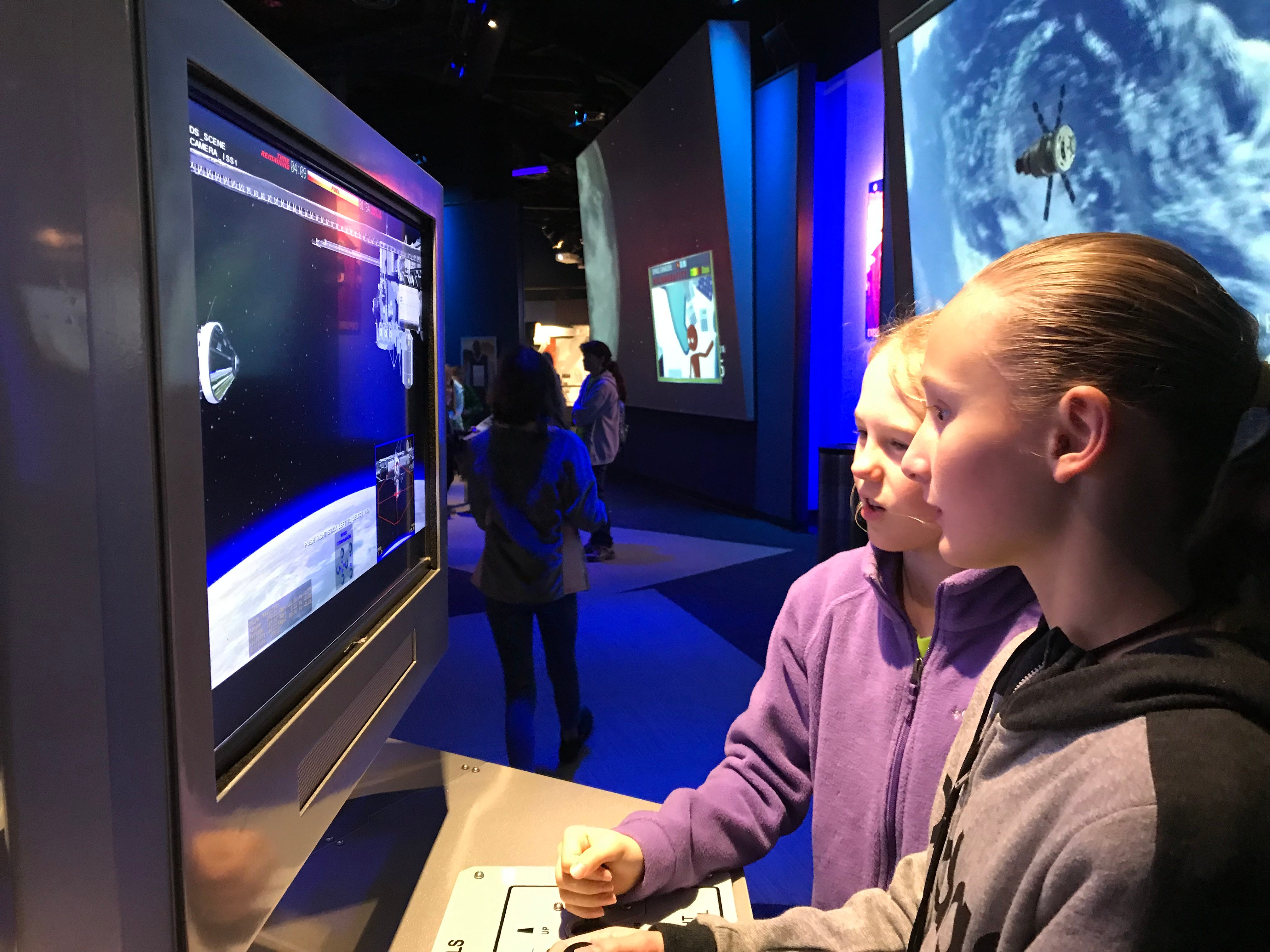 South Lake Elementary School students, Lexi Morris, 11, and Ada Howarter, 11, learn about launching a spacecraft at Journey to Mars at Kennedy Space Center Visitor Complex.