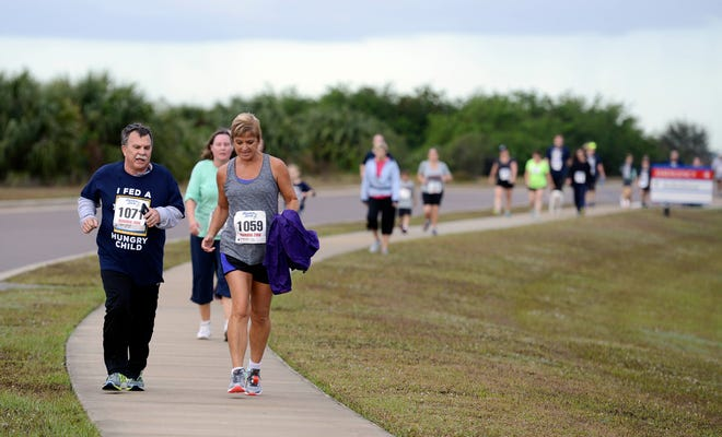 FLORIDA TODAY executive editor Bob Gabordi, left, and Lisa Rykaczewski walk in the inaugural Fight Child Hunger 5K in 2017.