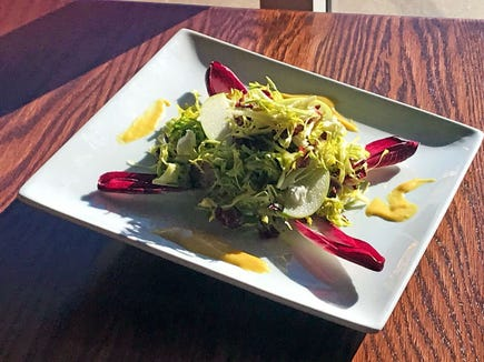 Frisée salad with apple, bacon, goat cheese tossed in an apple cider and honey mustard vinaigrette.
