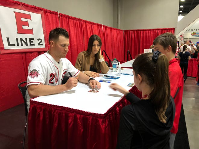 Anthony DeSclafani's wife, Lauren, looks on as the Reds starting pitcher signs for kids during Redsfest in December of 2018.