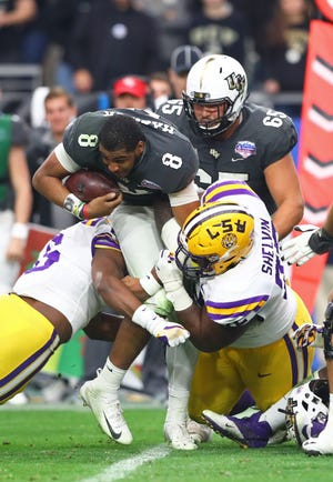 UCF quarterback Darriel Mack Jr. (8) loses his helmet as he is tackled by LSU Tigers nose tackle Tyler Shelvin (72) in the second half in the 2019 Fiesta Bowl at State Farm Stadium.
