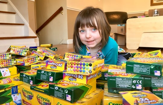 Brooklyn Brown, 5, of Huntington Woods is surrounded by the crayons she has collected for sick children. She has juvenile rheumatoid arthritis and wanted to do something to help other children who also have experienced the boredom that comes with hospitalization. She'll donate the crayons to area children's hospitals on Martin Luther King Day.