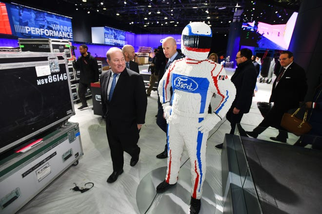 Detroit Mayor Mike Duggan walks past a Ford race car driver made out of Legos at the Ford display during a behind-the-scenes tour as construction continues on the North American International Auto Show at Cobo Center in Detroit on January 7, 2019.
