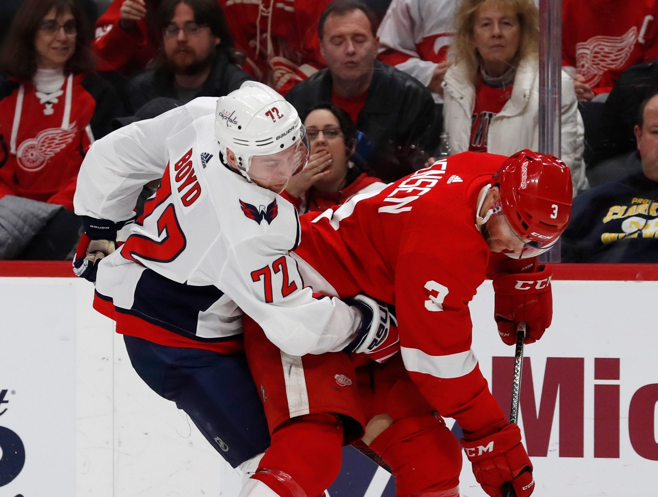 Washington Capitals center Travis Boyd (72) and Detroit Red Wings defenseman Nick Jensen (3) try controlling the puck during the second period.