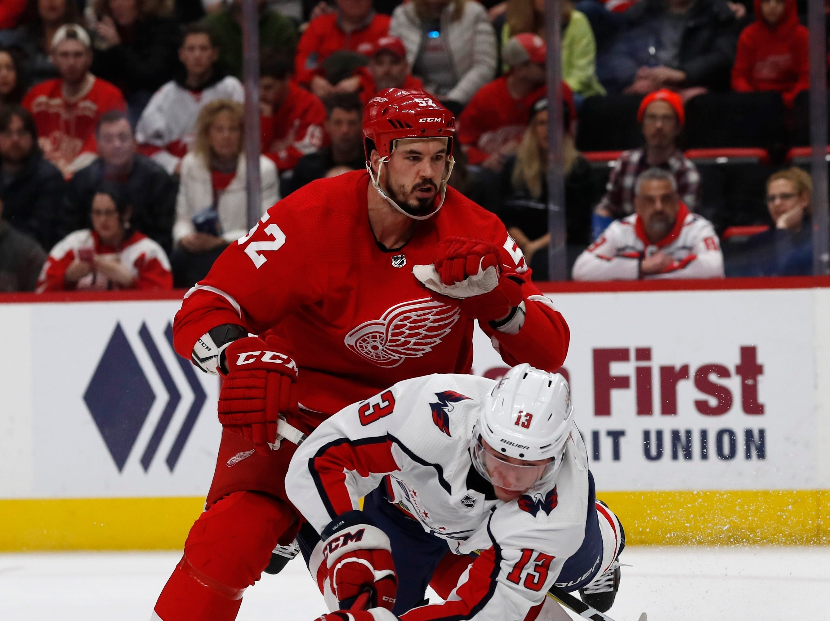 Washington Capitals left wing Jakub Vrana (13) is tripped by Detroit Red Wings defenseman Jonathan Ericsson (52) as he reaches for the puck during the second period.