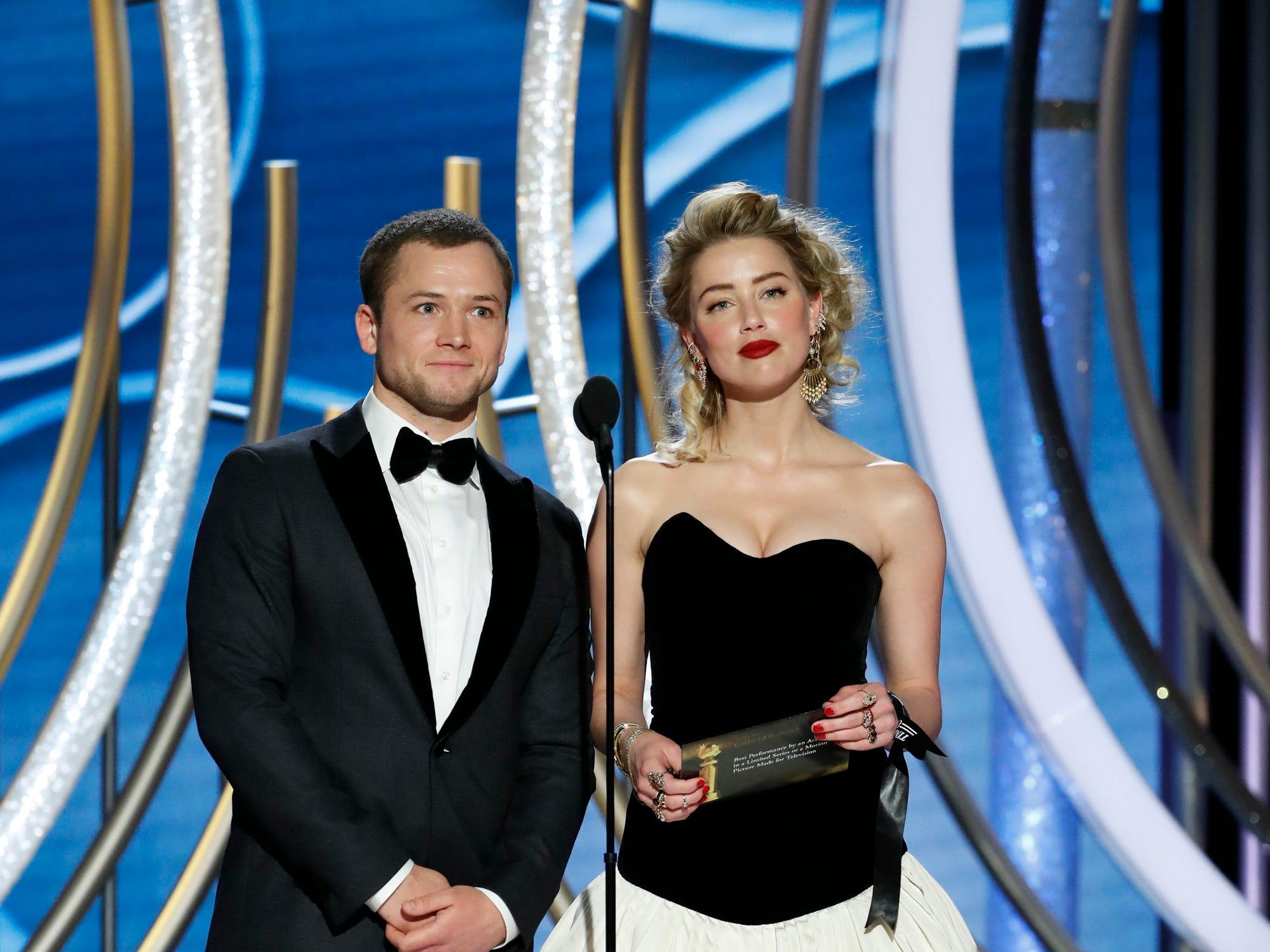 This image released by NBC shows presenters Taron Egerton, left, and Amber Heard during the 76th Annual Golden Globe Awards at the Beverly Hilton Hotel.