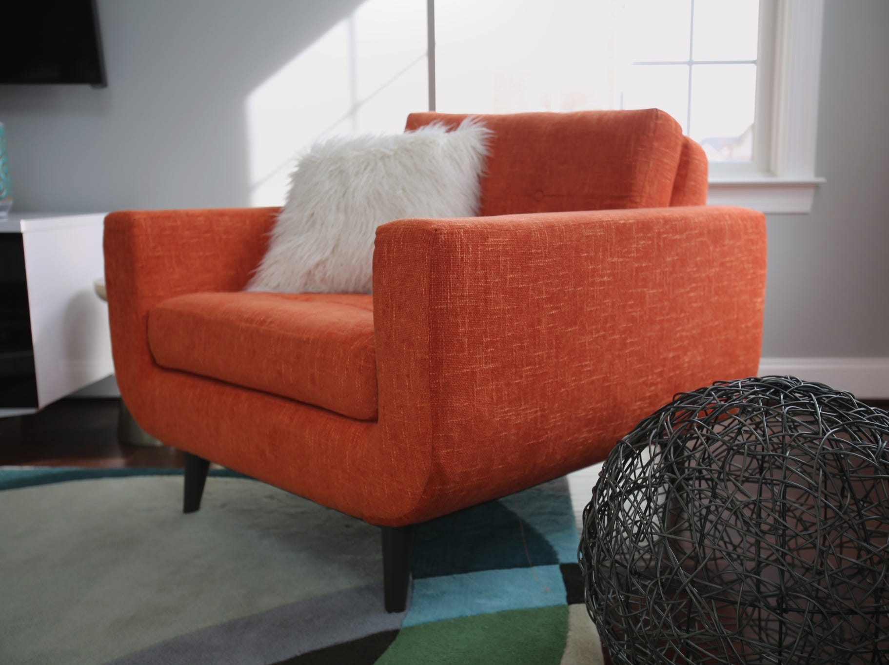 According to Dan Davis, large-scale accessories in the $50 range make a statement in any space, like the woven ball shown here (part of a pair) that accentuates the colorful midcentury-inspired chair.