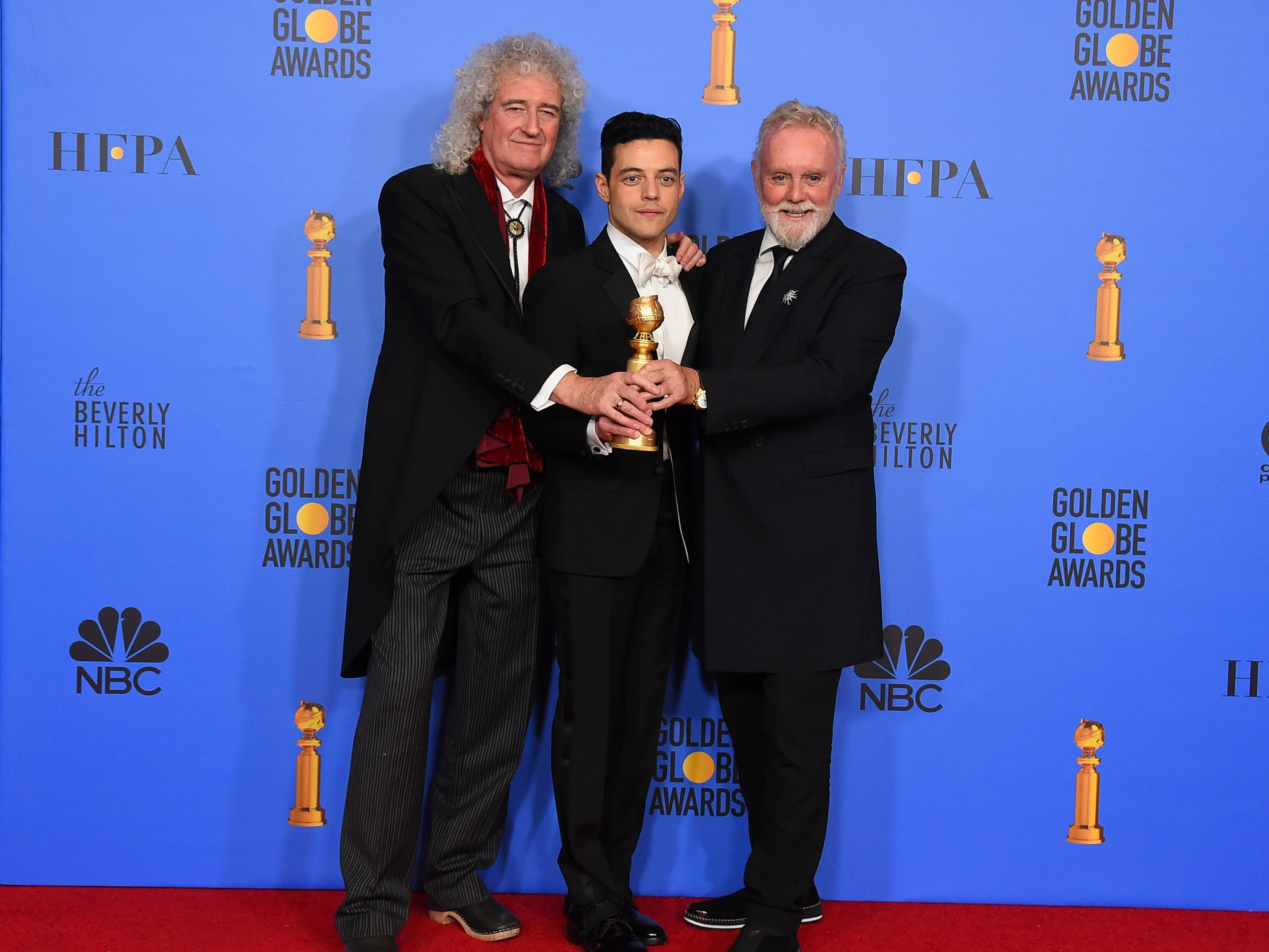 "Brian May, left, and Roger Taylor, right, of Queen, and Rami Malek pose in the press room with the award for best motion picture, drama for ""Bohemian Rhapsody"" at the 76th annual Golden Globe Awards at the Beverly Hilton Hotel."
