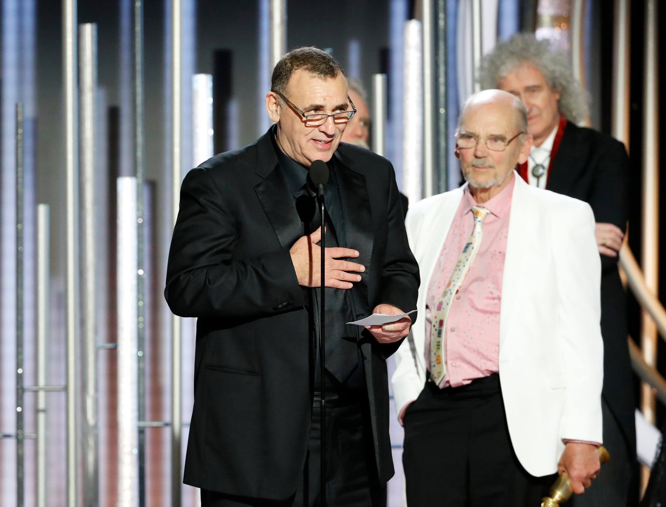 "This image released by NBC shows Graham King accepting the award for best motion picture drama for ""Bohemian Rhapsody"" as Jim Beach looks on, right, during the 76th Annual Golden Globe Awards."