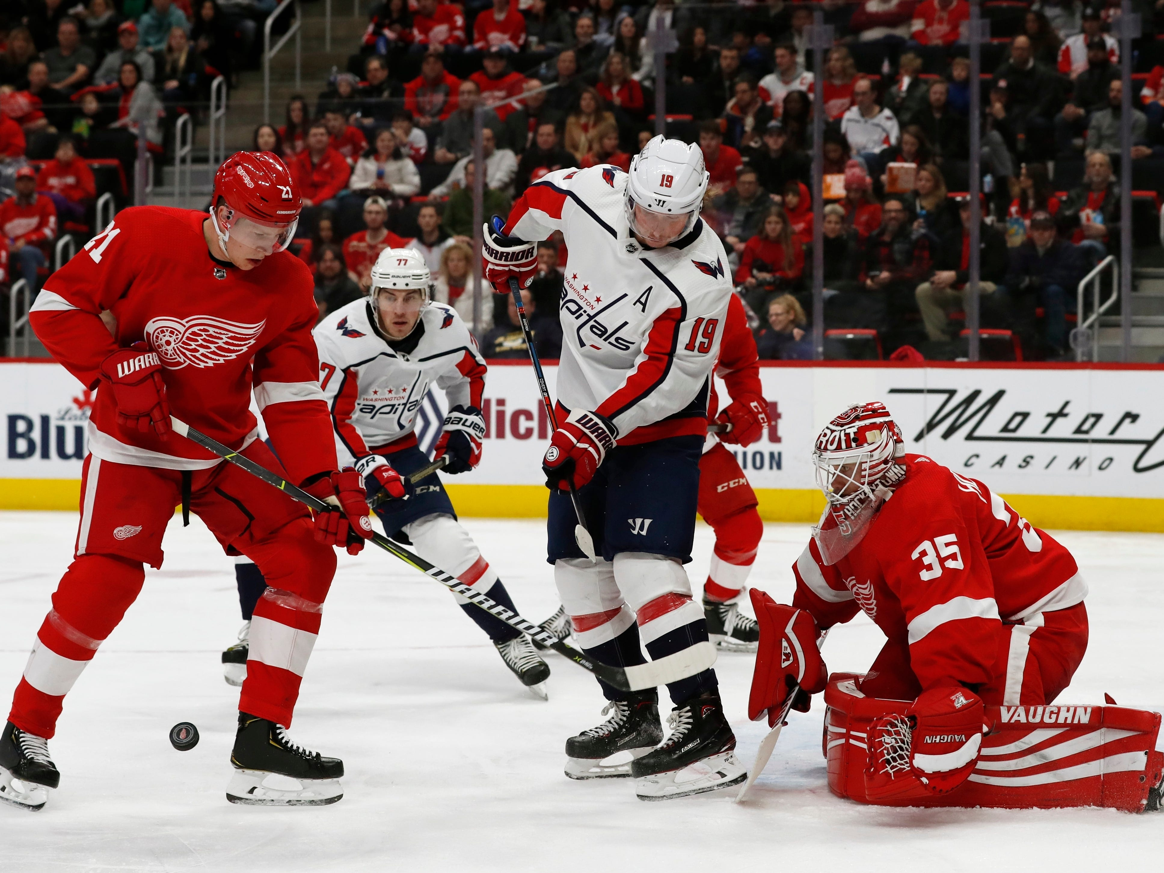 Detroit Red Wings defenseman Dennis Cholowski (21) helps deflect the puck away from Washington Capitals center Nicklas Backstrom (19) in front of goalie Jimmy Howard during the second period.