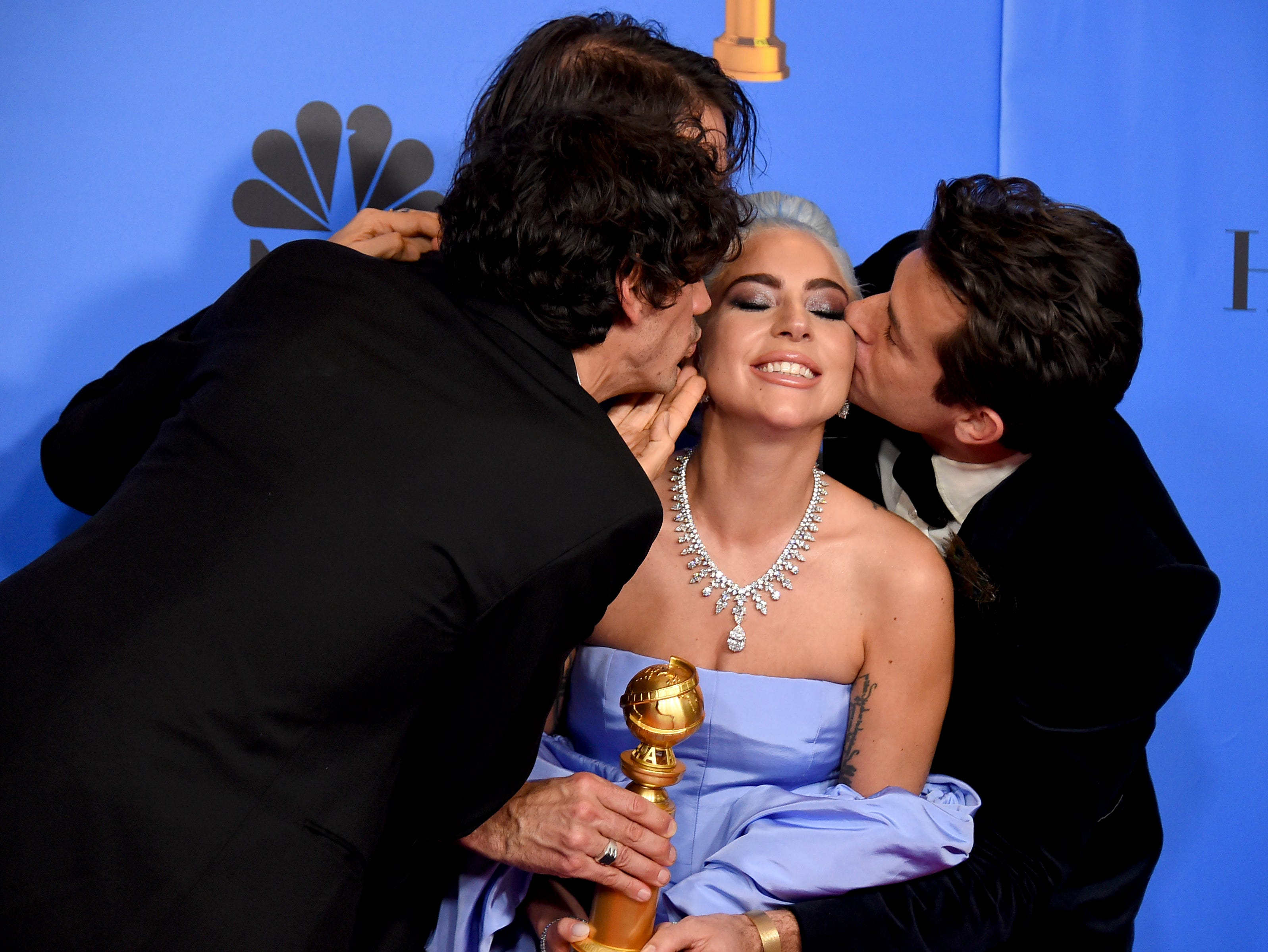 "Anthony Rossomando, from left, Andrew Wyatt, and Mark Ronson, right, kiss Lady Gaga, second right, as they pose in the press room with the award for best original song, motion picture for ""Shallow"" from the film ""A Star Is Born"" at the 76th annual Golden Globe Awards at the Beverly Hilton Hotel."