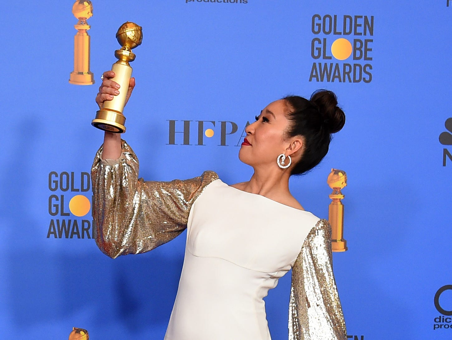 "Sandra Oh poses in the press room with the award for best performance by an actress in a television series, drama for ""Killing Eve"" at the 76th annual Golden Globe Awards."