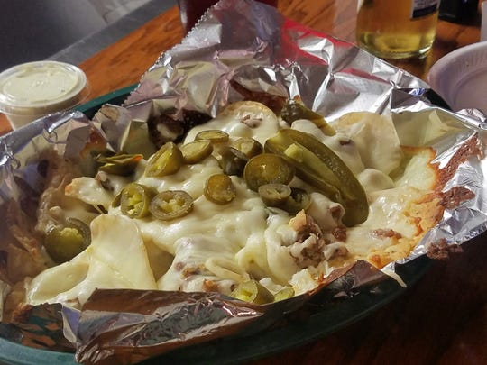 The steakhouse nachos from the Lobo Lounge, with thin-sliced beef, onion, bacon, jalapenos, cheese sauce, barbecue and mozzarella cheese.