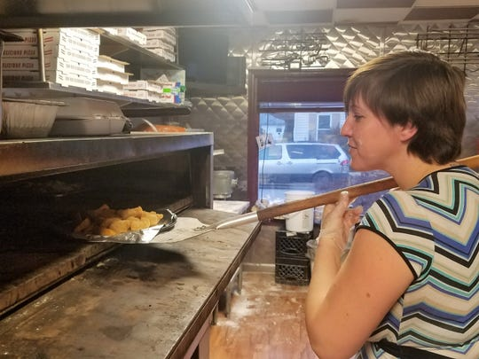 Robin Redden Hobgood, co-owner and daily manager of The Lobo Lounge, places an order of boneless wings cooking in the pizza oven to cook.
