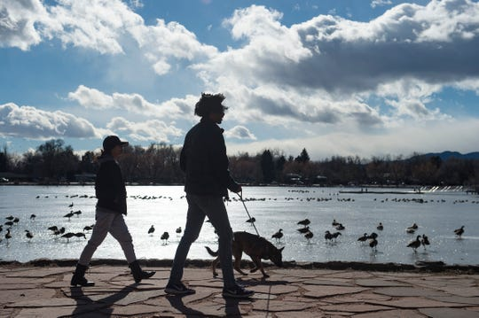 Mercedes Renshaw and Brandon Hunt walk their dog, Django, around Sheldon Lake in City Park on Monday. The city of Fort Collins is looking for applicants to attend a two-day workshop in March and provide input on the park's future.
