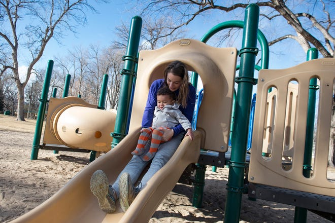 Allison Wright holds her son, Miles, 1, as the two take a ride down a slide at City Park on Monday. Fort Collins officials are looking for applicants to attend a two-day workshop in March and provide input on the park's future.