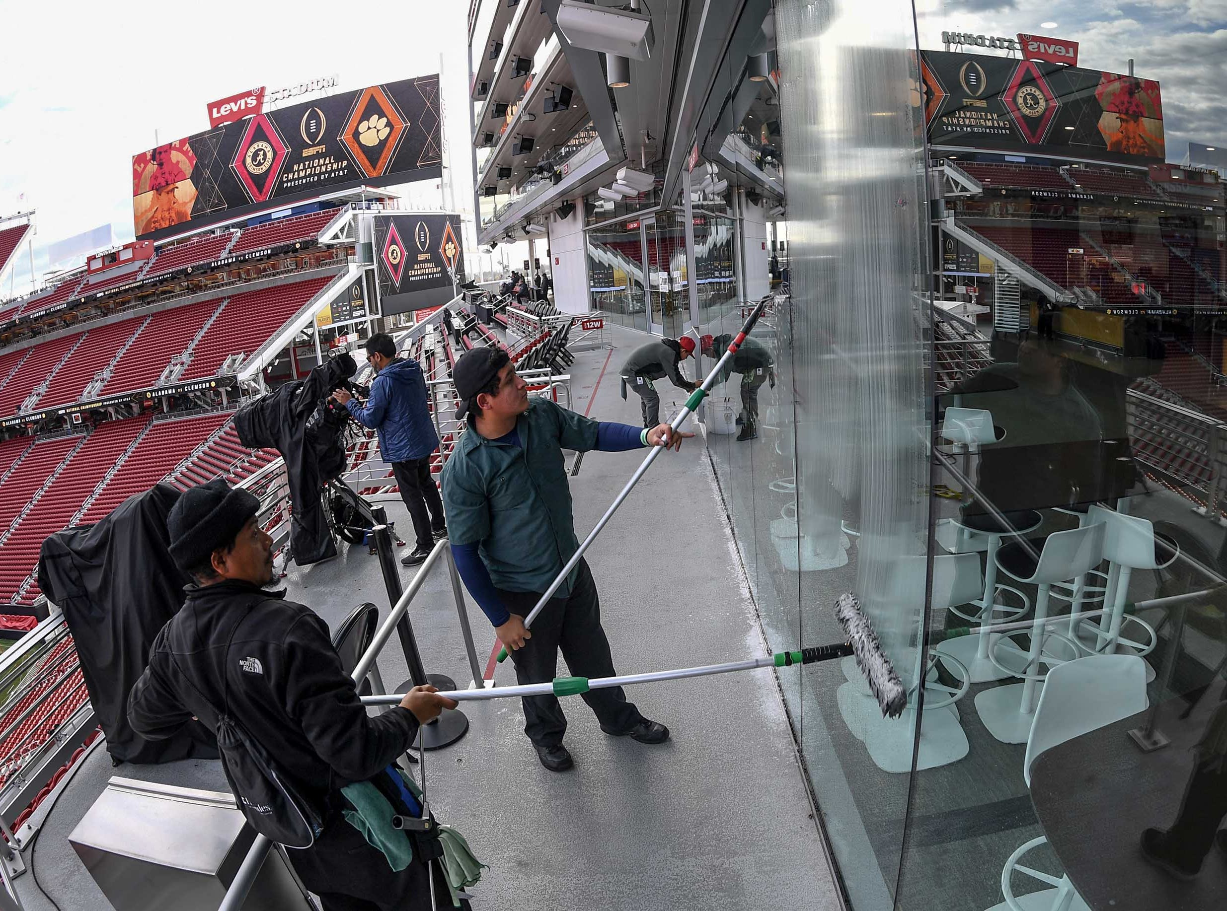 Window cleaners work as many officials prepare before the kickoff during the College Football Championship at Levi's Stadium in Santa Clara, California Monday, January 7, 2019.