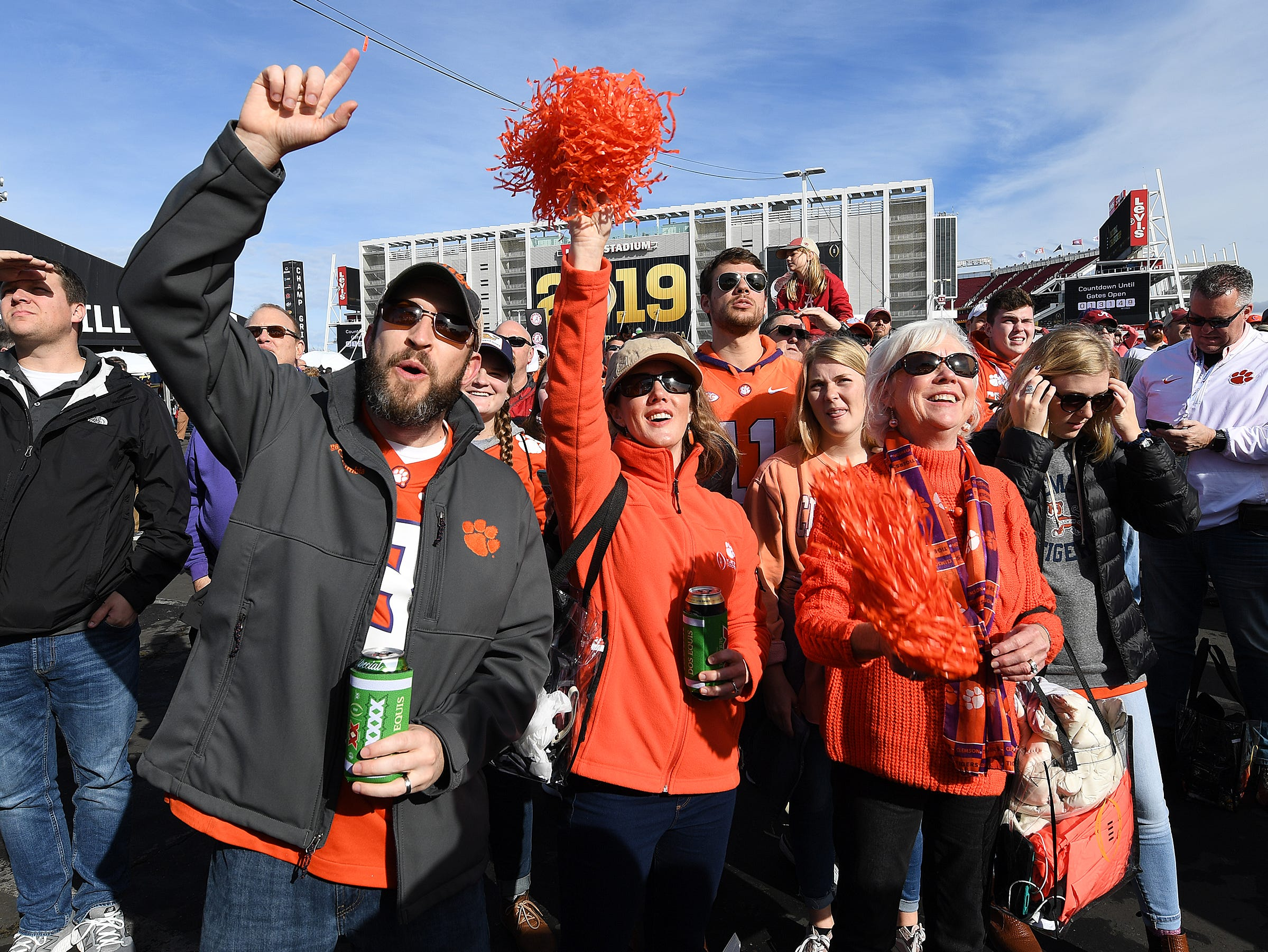 Brandon and Chisty Spencer, left, and Darlene Altman cheer during the College Football Championship Playoff Tailgate outside Levi's Stadium in Santa Clara, CA Monday, January 7, 2019.