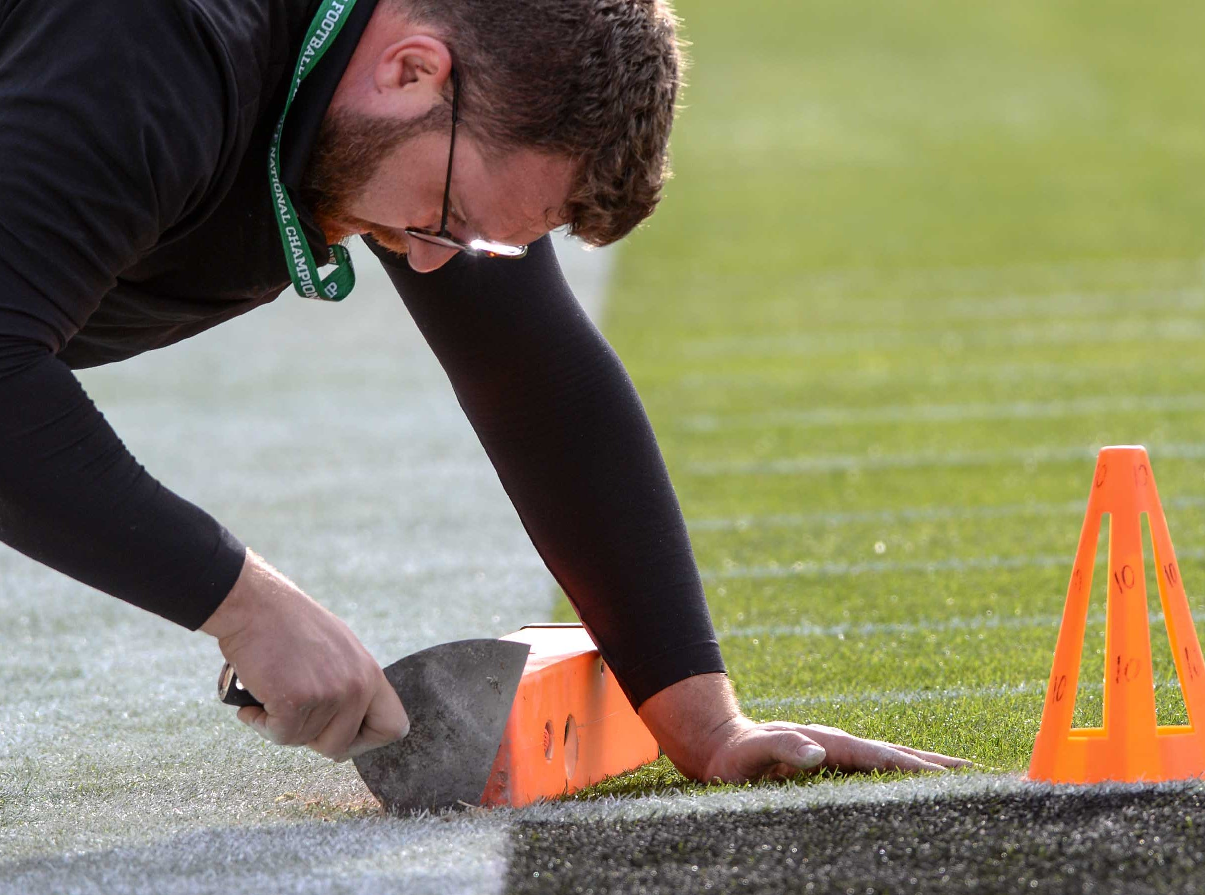 Mark McGee fixes an end zone camera marker in the grassy field as officials prepare before the kickoff during the College Football Championship at Levi's Stadium in Santa Clara, California Monday, January 7, 2019.