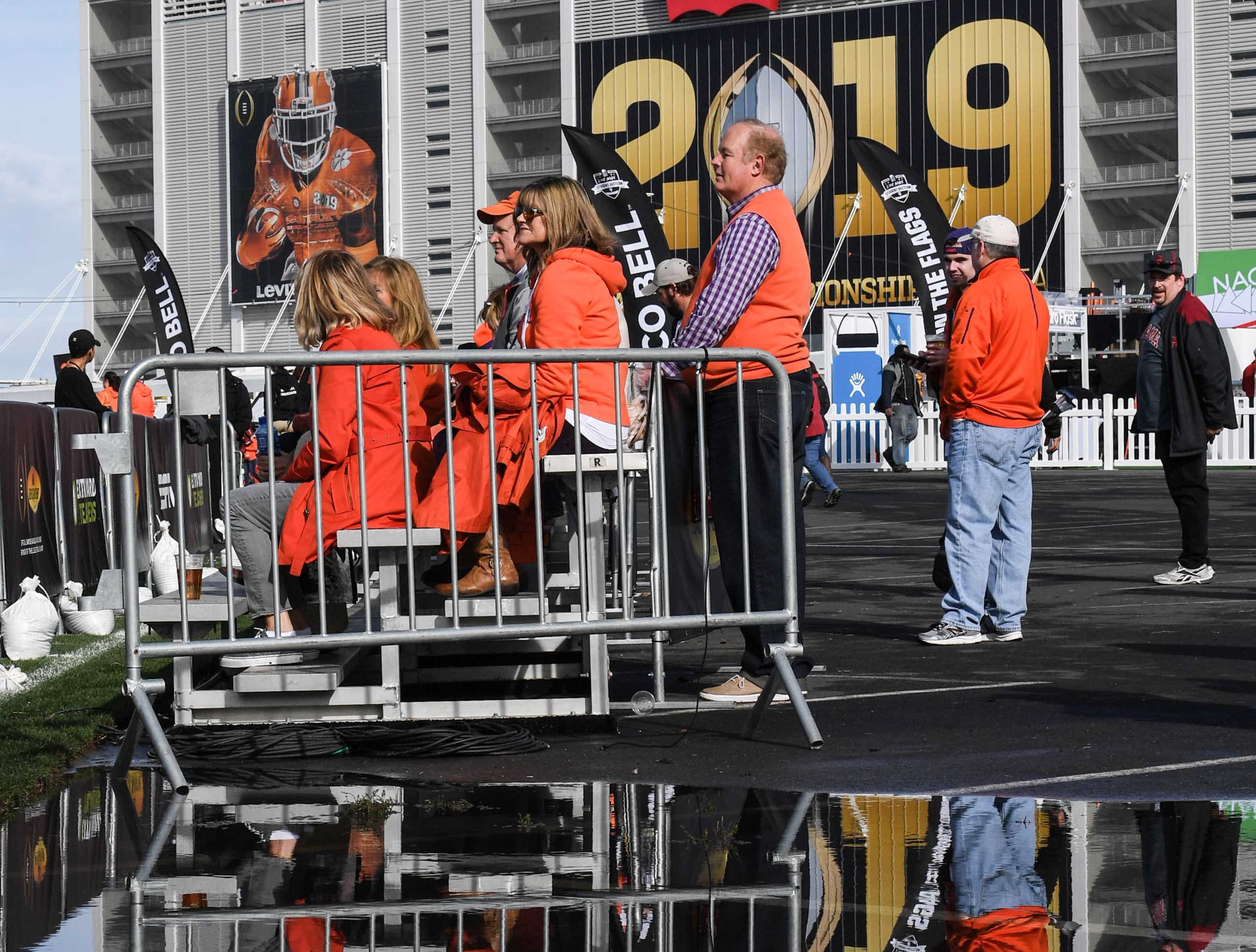 Clemson fans stand near a puddle of water from recent rain, participating in the College Football Championship Playoff Tailgate outside Levi's Stadium in Santa Clara, California Monday, January 7, 2019.