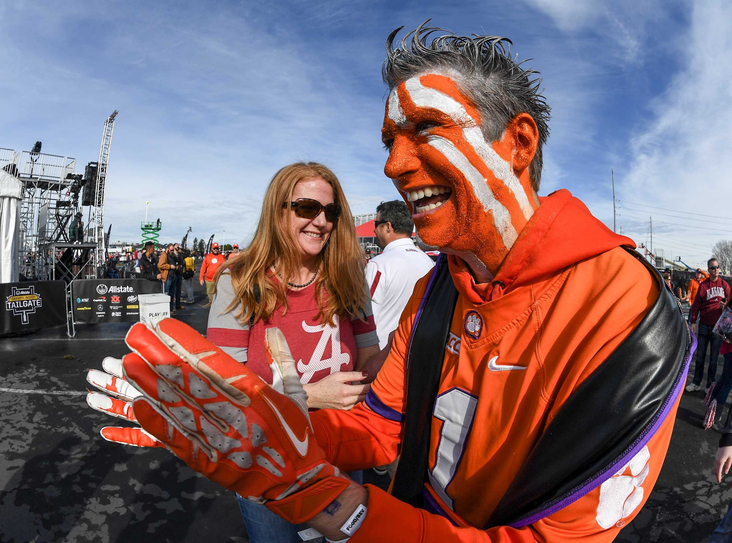 Clemson fan Peter Rowan, right, calling himself MVPeter, is greeted by an Alabama fan as he participates at the College Football Championship Playoff Tailgate outside Levi's Stadium in Santa Clara, California Monday, January 7, 2019.