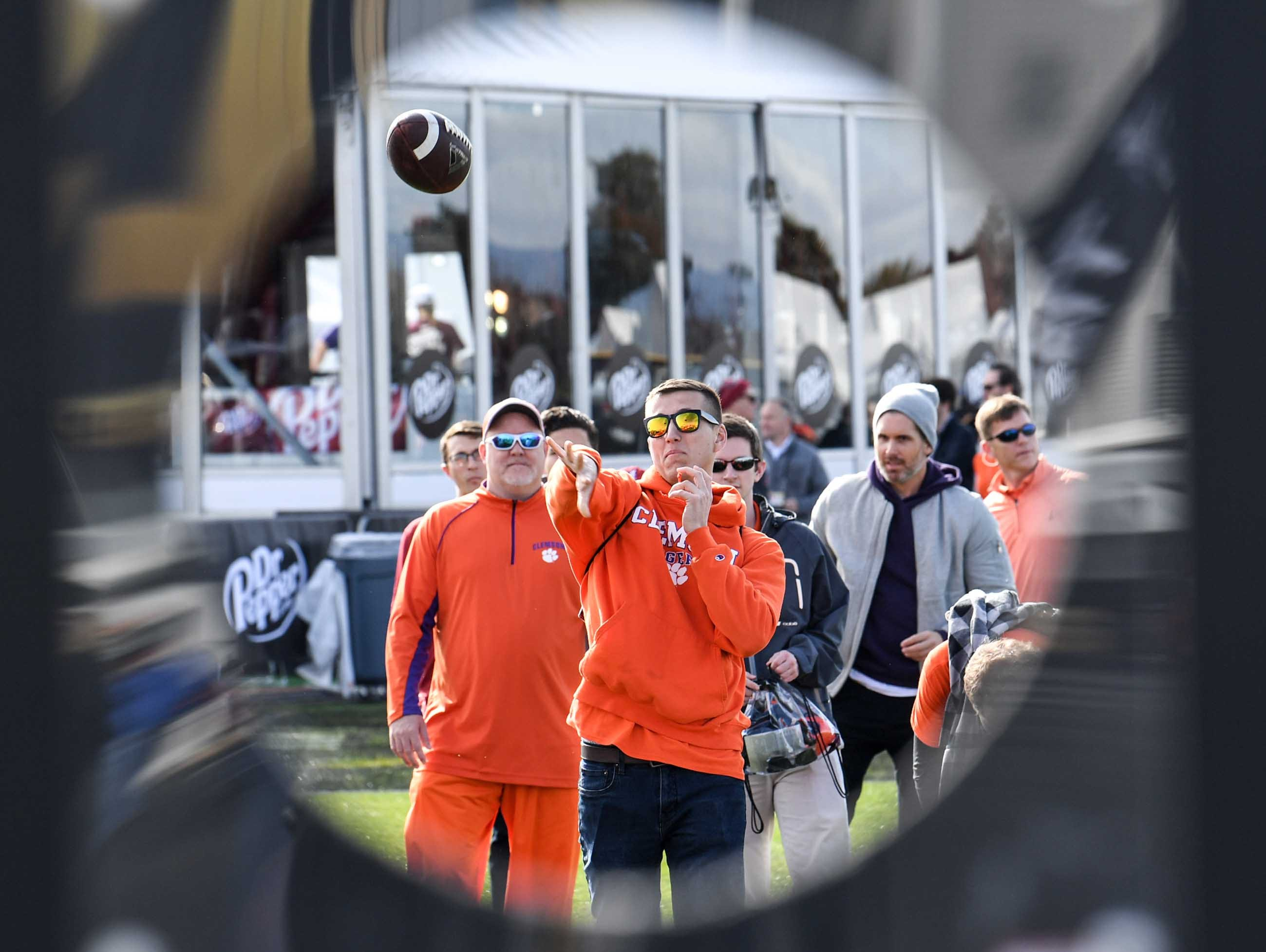 Clemson fan Matt Diener, class of 2017, of San Diego, tosses a football at the College Football Championship Playoff Tailgate outside Levi's Stadium in Santa Clara, California Monday, January 7, 2019.
