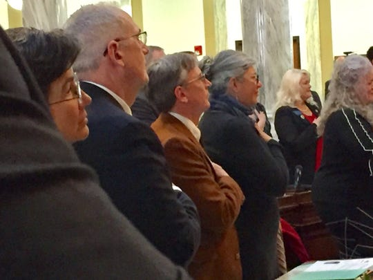 Lawmakers stand for the national anthem in Helena.