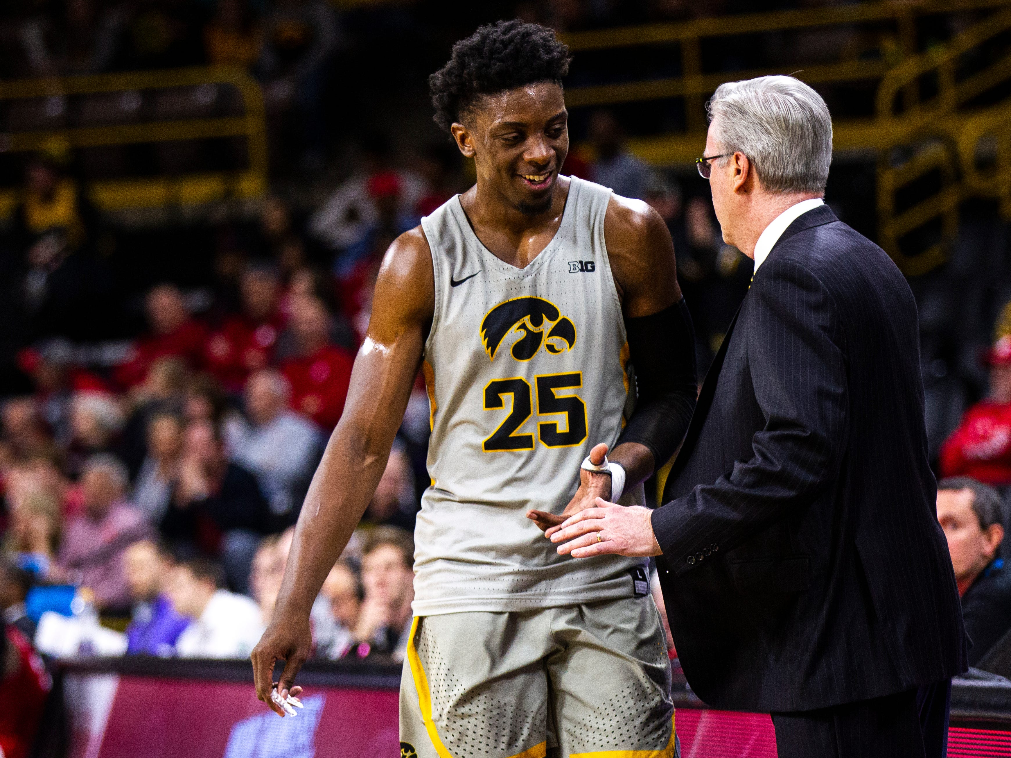 Iowa forward Tyler Cook (25) smiles while he talks with Iowa men's basketball head coach Fran McCaffery as he heads to the bench during a NCAA Big Ten Conference men's basketball game on Sunday, Jan. 6, 2019, at the Carver-Hawkeye Arena in Iowa City, Iowa.