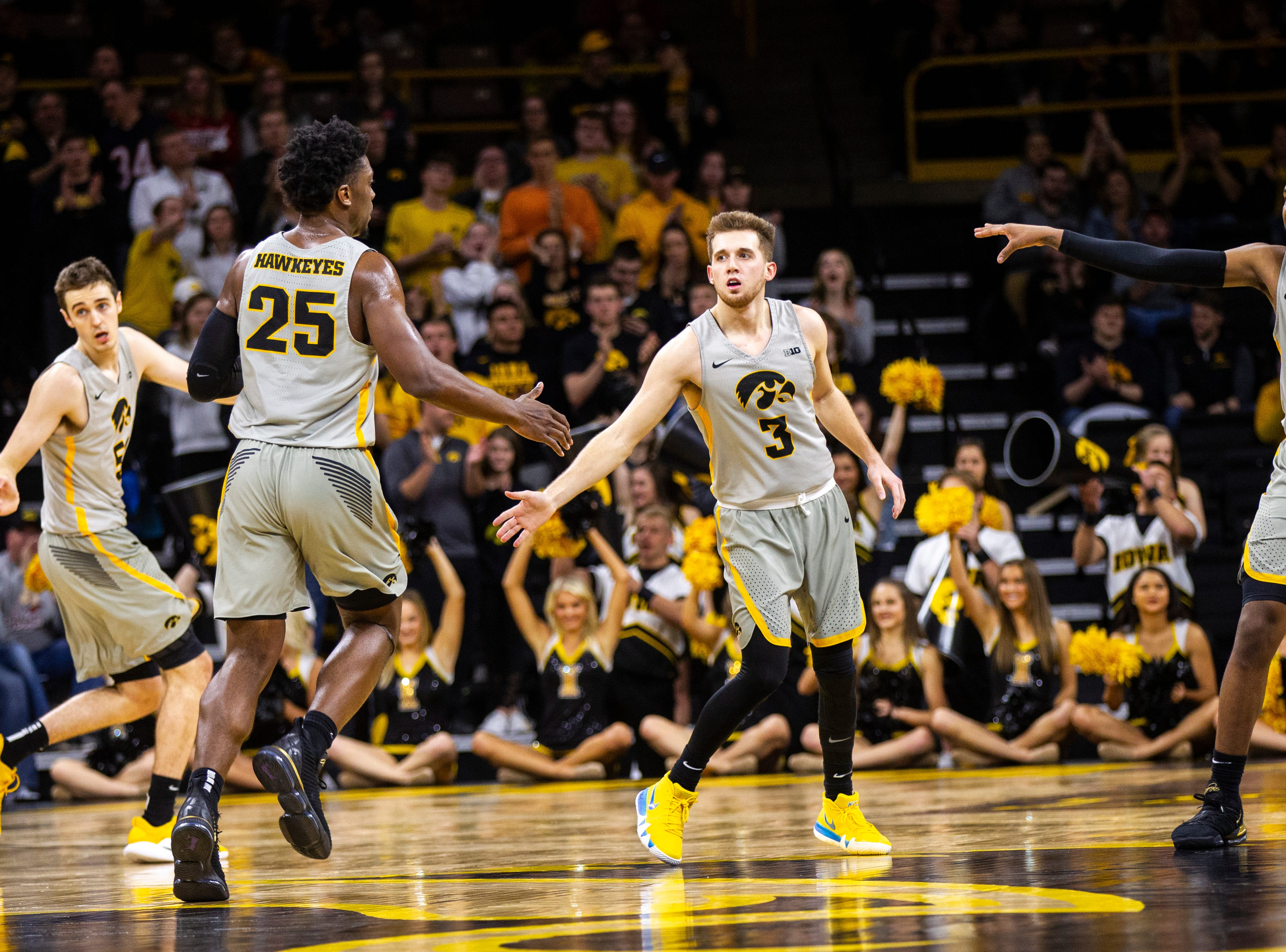 Iowa guard Jordan Bohannon (3) gets a high-five from Iowa forward Tyler Cook (25) while teammates Nicholas Baer (51) and Isaiah Moss (4) settle in on defense during a NCAA Big Ten Conference men's basketball game on Sunday, Jan. 6, 2019, at the Carver-Hawkeye Arena in Iowa City, Iowa.