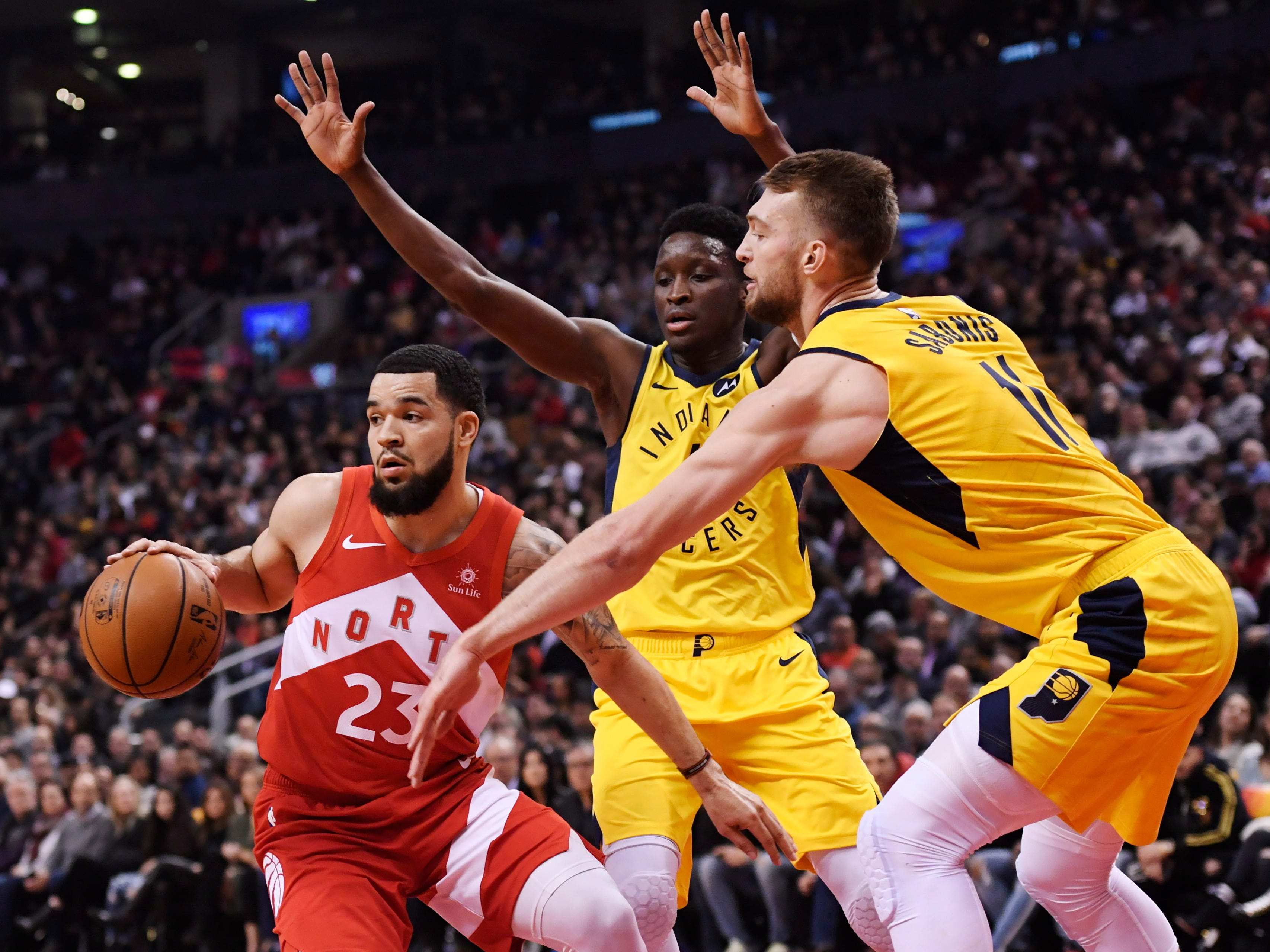 Toronto Raptors guard Fred VanVleet (23) protects the ball from Indiana Pacers guard Victor Oladipo (4) and forward Domantas Sabonis (11) during first half NBA basketball action in Toronto on Sunday, Jan. 6, 2019.