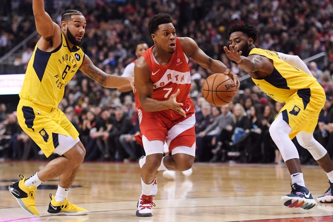 Toronto Raptors guard Kyle Lowry (7) drives between Indiana Pacers guard Cory Joseph (6) and guard Tyreke Evans (12) during first half NBA basketball action in Toronto on Sunday, Jan. 6, 2019. (Nathan Denette/The Canadian Press via AP)