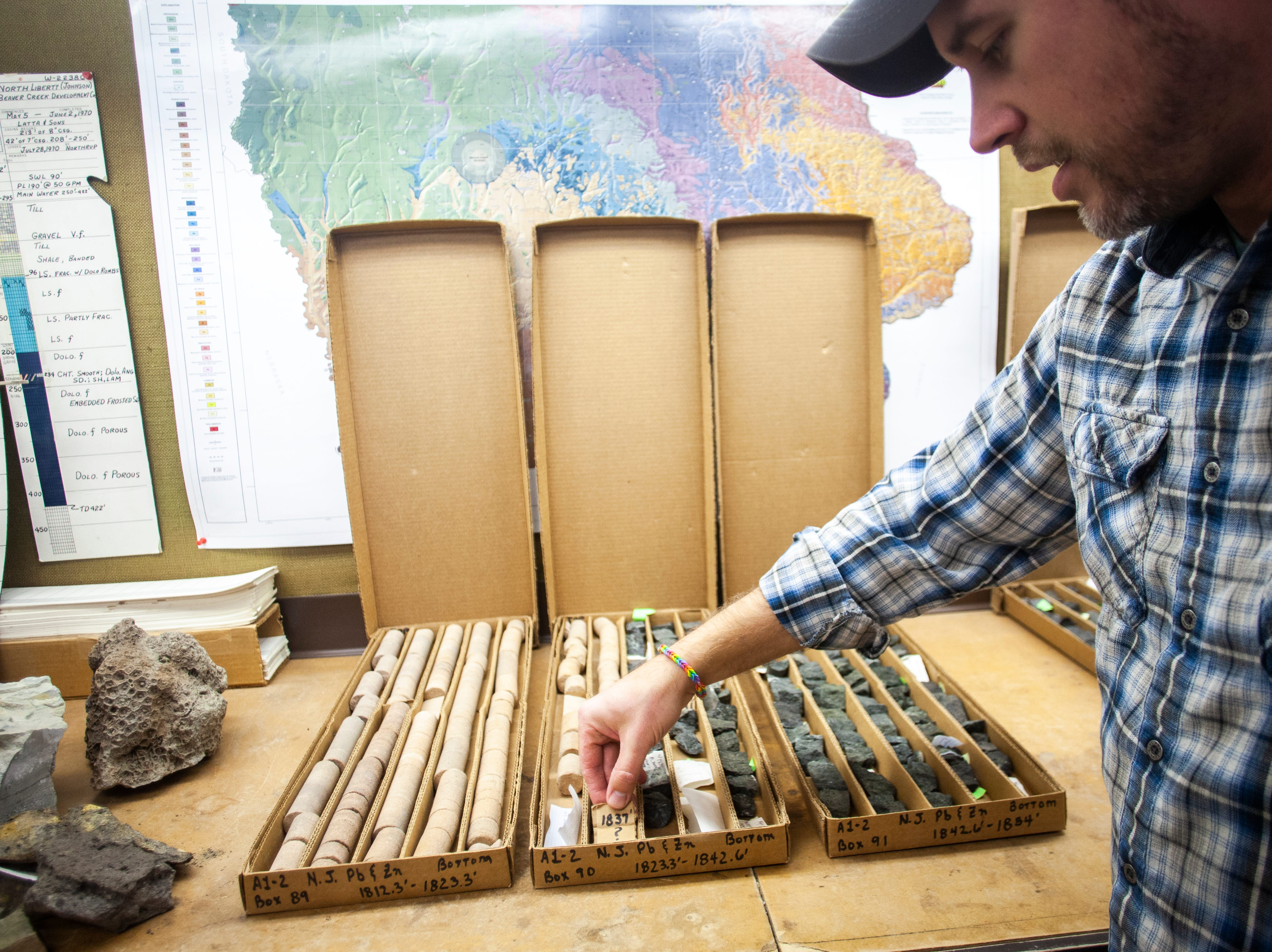 Ryan Clark of the Iowa Geological Survey describes the transition that the halves of core samples taken in northeast Iowa show with sandstone in the upper left and transitioning into a darker, potentially mineral rich rock, on the right, on Monday, Jan. 7, 2019, at his office in the at UI Oakdale Research Campus in Coralville, Iowa.